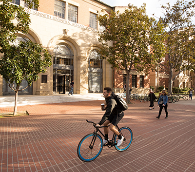 A student rides his bike by the Accounting building.