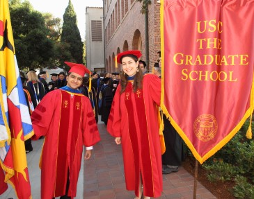 Two graduate students take part in Commencement.