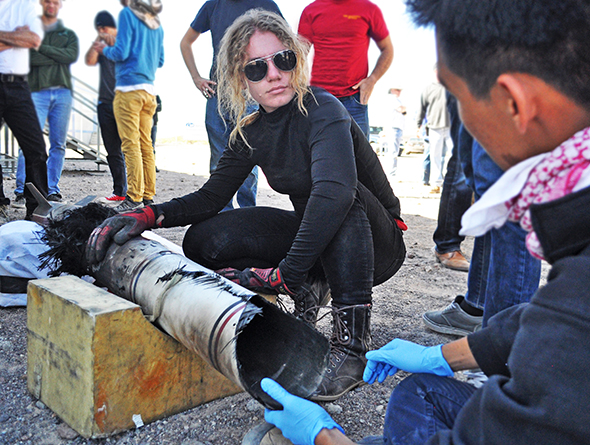 Students examine a segment of scorched rocket fuselage.